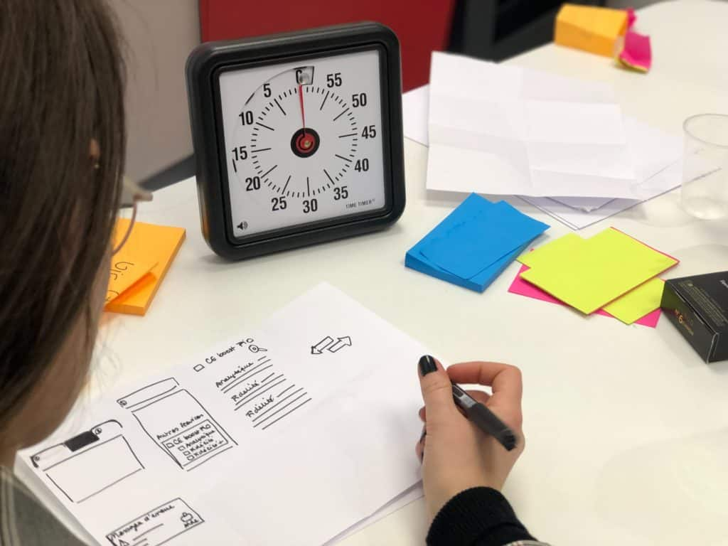 A table with a woman drawing smartphone interfaces on a sheet of paper. A timer and post-it's surround her.